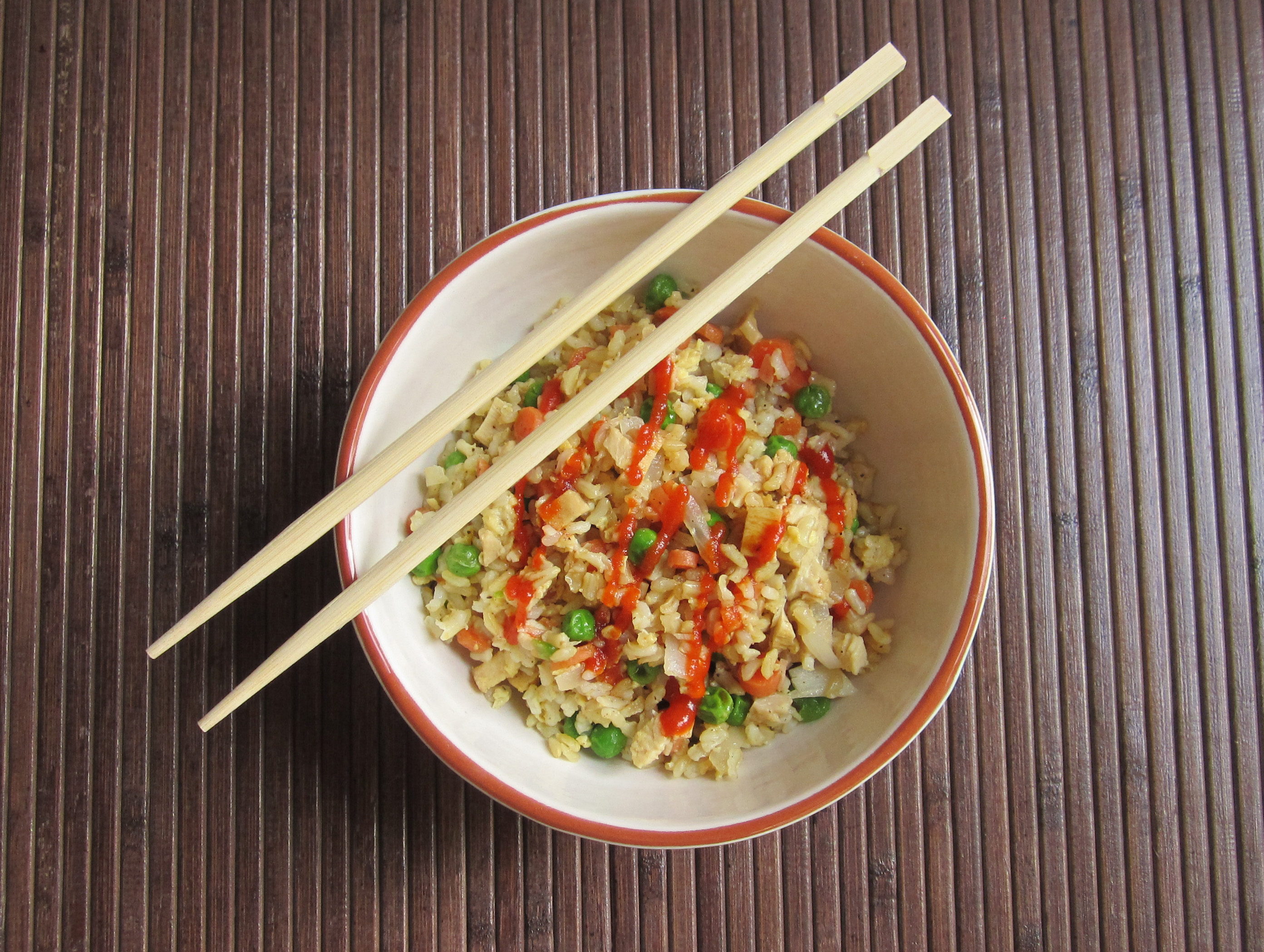 a bowl of homemade chicken fried rice with vegetables.